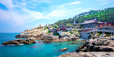 Busan Temple on the coast, with rocks and green and blue water.
