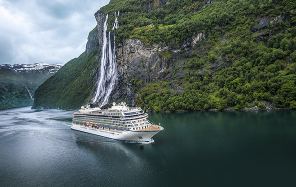 A Viking ocean ship sailing past the Seven Sisters Waterfall in Geiranger, Norway
