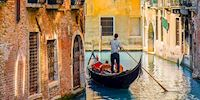 Several people in a gondola sailing through the canals of Venice, Italy