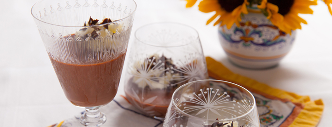 Chocolate Hazelnut Panna cotta served in an etched crystal goblet with bright sunflowers in the background.