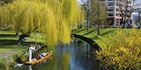 People riding in a gondola on the Avon river in Christchurch, Australia