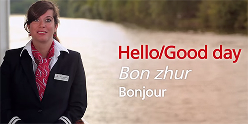 "A woman in a black blazer with the words ""Hello"" in English and French overlayed in white text."