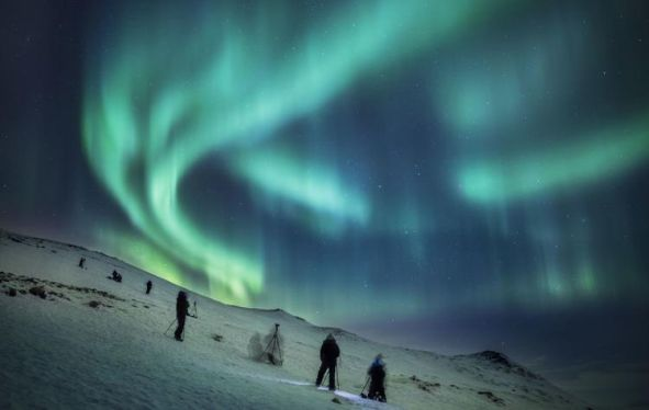 Climbers at night, on a snowy mountainside with the northern lights glowing green above them.