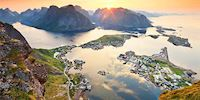 The sun sets behind mountains coming out of the sea in Lofoten Islands