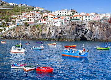 Colorful boats in the water by Câmara de Lobos