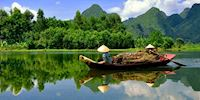 Two Mekong boatmen paddle down the river along the lush forest