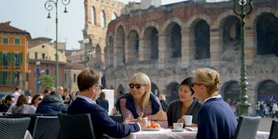 Group of people sitting at a table having coffee in Rome, Italy.