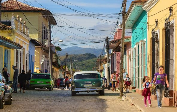Colorful buildings and classic cars on the road in Cuba.